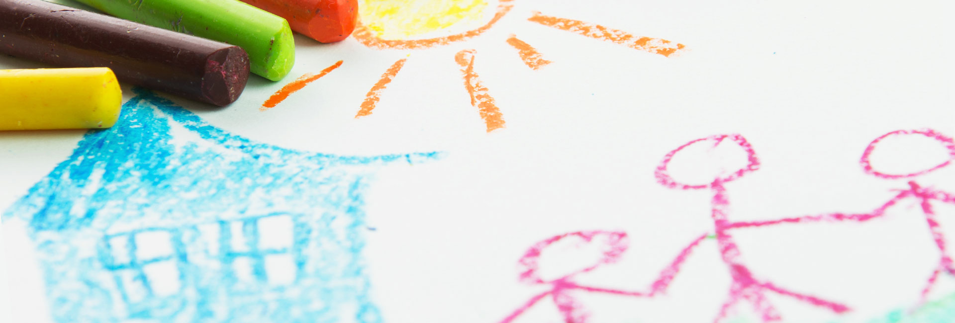 Child's crayon drawing showing sun, house and family